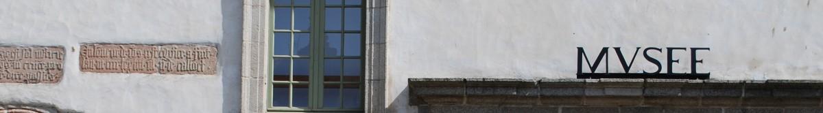 Cinq lettres noires de style antique sont posées au dessus d'une longue pierre qui semble être le haut d'un porche. Ces lettres indiquent l'entrée du Musée de Morlaix. Elles écrivent MUSEE. Sur la moitié gauche de ce bandeau une fenêtre et des pierres comportant des inscriptions ressortent de la pâleur de ce mur du bâtiment des Jacobins.