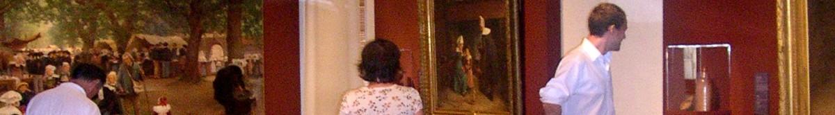 """Le bandeau horizontal de cette page est un détail d'une photographie réalisée lors de l'exposition """"Bretons, Bretonnes"""" en 2005. Le haut du corps de trois visiteurs ( bustes et têtes) apparait sur le fond bordeaux et blanc des murs de la salle d'exposition. Trois œuvres posées sur ces murs et une bouteille sous vitrine) sont également en partie visibles."""