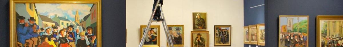Sur ce bandeau, un détail d'une photo prise lors du montage de l'exposition consacrée à Pierre de Belay. Les murs présentent une enfilade d'œuvres encadrées, des scènes bretonnes. Au milieu, un escabeau vient perturber l'image. Sur cet escabeau,un homme dont on ne voit que les jambes est debout. Que fait-il? L'image ne permet pas de le savoir.