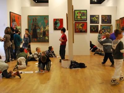 format paysage - Cette image très colorée a été réalisée dans la salle d'exposition consacrée à André Marchand à Morlaix en 2010. Aux deux extrémités de l'image des portraits de l'artiste apparaissent sur des grands panneaux explicatifs. Tout le reste de l'image est occupée par les murs d'exposition sur lesquels sont présentés une quinzaine d'œuvres très colorées et de tous formats. Devant, une vingtaine d'enfants d'environ 6 ans remplissent la salle. Certains posés au sol, d'autres se croisent dans tous les sens. Ils travaillent, ou plutôt s'amusent avec leur livret-jeune public conçu par le service éducatif du Musée de Morlaix.