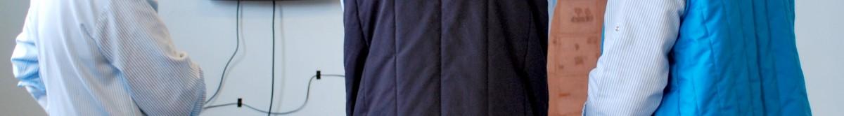 """Dans une salle aux murs bleus pales et au sol recouvert d'une moquette marron, trois femmes debout, de dos regardent une exposition. Sur les murs, les tableaux représentant des paysages et une œuvre abstraite. Un écran de télévision vient compléter cet ensemble qui constitue une partie de l'installation conçue par Catherine Rannou lors du projet intitulé """"Une ville ne sera jamais finie!"""". La fonction de ces femmes dans le Lycée est clairement identifiable en raison de la tenue qu'elles portent. Ce sont des femmes chargées de l'entretien. Elles portent des pantalons, des blouses et des blousons sans manches tous bleus. Ces différents bleus des tenues vestimentaires rappellent la couleur des murs de la salle qui allait redevenir une salle de cours quelques jours après la fin de l'exposition."""