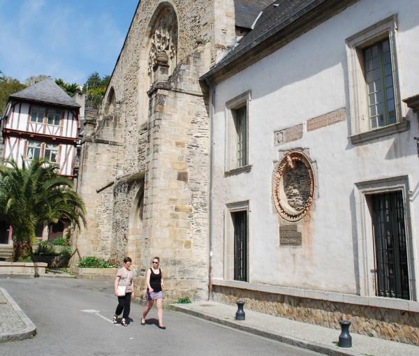 Cette photo offre une vue d'une partie de la façade du site des Jacobins. Au premier plan, sur la droite, se trouve une partie du bâtiment conventuel (c'est à dire du couvent). Deux femmes se dirigent vers l'entrée du Musée en marchant. Dans le prolongement de cette façade, se dresse l'église des Jacobins. Tout au fond de cette image, une jolie maison à pans de bois rouges, perpendiculaire à l'église laisse deviner le passage de la rue des Vignes qui longe le site des Jacobins.