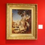 """Sur un mur rouge, est posé le tableau de Charles Longueville. Ce tableau présenté dans un grand cadre doré représente l'entrée d'un marché à Beyrouth au début du XIXeme siècle. Au premier plan, à droite, un homme de face, passe devant l'entrée du souc menant son chameau (ou dromadaire) dans une lumière doucement ombragée. A gauche, deux hommes et une jeune femme assis dans la lumière regardent un chien qui """"fait le beau"""". Au deuxième plan, la lumière est très forte, des personnages déambulent devant une mosquée. la partie haute du tableau est coupé en deux. A gauche une grande réserve de bleu indique que le ciel est dégagé et justifie la lumière plombante. A droite le feuillage d'un arbre justifie l'ombre qui couvre une bonne partie du premier plan."""