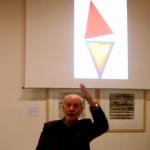 Sous un écran, dans l'obscurité d'une salle, un homme apparait en buste. Il est face à son public, hors champs, il parle en levant la main gauche pour appuyer son propos. Il s'agit de Claude Briand Picard lors d'une conférence au Musée de Morlaix. Sur l'écran est projetée une œuvre de ses œuvres. Il s'agit de la photo d'une sculpture de l'artiste composée de deux triangles colorés de rouge pour l'un, de bleu de rose et de jaune pour l'autre.
