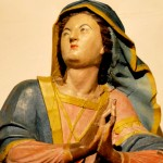 Cette sculpture en bois polychrome représente Ste Geneviève vêtue d'une tenue, bleue, rose et jaune. Ce même bleu et ce jaune se retrouvent dans le tissu qui lui recouvre la chevelure. Son visage est tourné vers le ciel et elle joint les mains pour la prière. Ce format carré n'offre qu'un détail de cette sculpture en pied, de la collection du Musée de Morlaix.