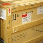 cette image réalisée pour illustrer le transport des œuvres est une photographie d'une caisse en bois spécialement dédiée aux déplacement des objets fragiles. Sur les trois faces de cette caisse, des lettres, des étiquettes attestent de nombreux déplacements déjà réalisés.