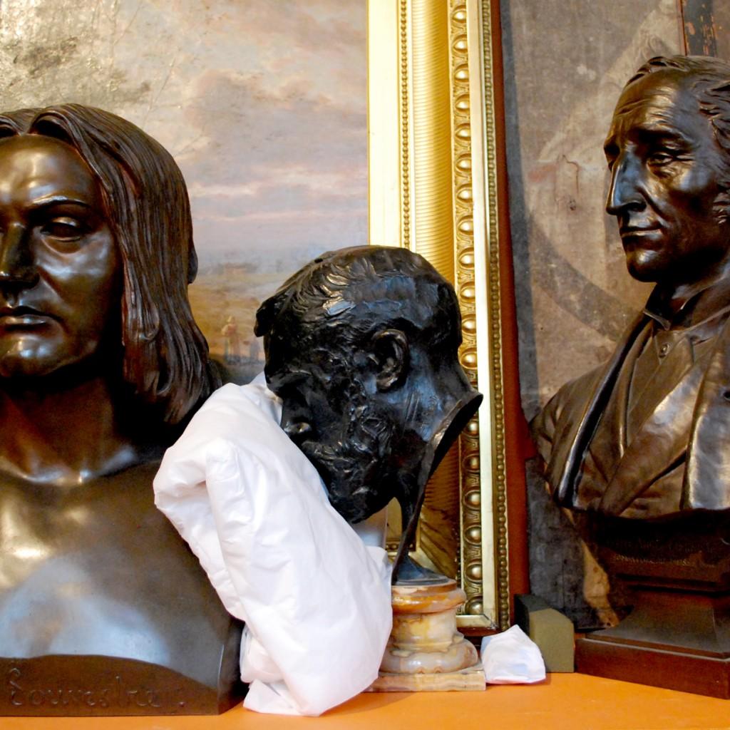 Dans ce cliché au format carré réalisé dans les réserves du Musée de Morlaix, trois bustes sont posés l'un à côté de l'autre. Au centre, de profil se trouve celui de Gustave Geffroy, écrivain et critique. Devant son visage, une protection vient prévenir tout contact avec le buste d'Emile Souvestre, écrivain, vu de face. A droite, un peu plus haut, le buste du Comte Ange de Guernisac, bienfaiteur du Musée de Morlaix semble surveiller les deux autres. Au fond, une toile au cadre doré et un panneau de bois peint viennent compléter la composition.