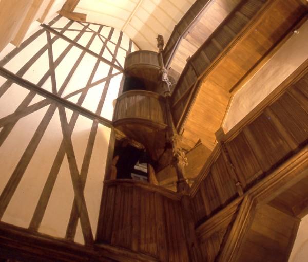 Ce cliché réalisé par le photographe RV Ronné est une vue en contre plongée de l'escalier dans la Maison à Pondalez du 9 Grand'Rue à Morlaix. Au centre de cette photo, un escalier à vis monte sur trois étages. Sur la partie droite, à chaque niveau, un balcon avec une main courante joliment sculptée dans un style gothique flamboyant. De l'autre coté de l'image, à gauche de l'escalier un grand mur intérieur montre le joli dessin des pans de bois coupés par une croix de st André. Ces éléments architecturaux montent jusqu'au toit que l'on voit dans la partie supérieure de l'image.