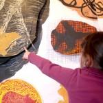 """Dans le bas à droite de l'image une petite fille, de dos, montre du doigt un détail qu'elle a remarqué sur une grande œuvre qui remplit tout le reste du format. C'est une estampe sur laquelle de grands formes oblongues de couleur (jaune, orange rose et noir) sur fond blanc ont été collées après avoir été imprimées. Il s'agit d'une œuvre de Nicolas Fedorenko présentée au Musée de Morlaix à l'occasion de l'exposition"""" un peintre dans la ville, la position de l'incertitude"""" en 2007."""