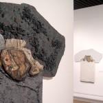 Les trois quarts de cette image sont occupés par un mur blanc sur lequel est posé une œuvre contemporaine réalisée par l'artiste Jean Vaugeois. Cette étrange forme en contreplaqué recouvert de peinture mélangée à du sable est traitée dans des couleurs sombres. Des pièces de cartons sont collées sur ce panneau qui n'apparait qu'en partie. A droite, sur le dernier quart, sur un autre mur au second plan, une œuvre est appréciable dans son entité. Les formes sont proches de la première, par contre celle ci est traitée dans des teintes blanches à l'exception du carton qui garde là aussi ses couleur d'origine.