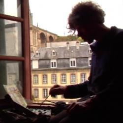 Au premier plan, un homme, de profil en contre-jour, assis sur le rebord d'une fenêtre, peint sur un petit support. Derrière lui un bâtiment jaune avec de nombreuses fenêtres et une toiture surmontée de deux petites cheminées, laisse peu de place à une église que l'on devine à peine. Deux arches du Viaduc sont visibles dans le haut du paysage, sur la gauche. Ce peintre est Ricardo Cavallo qui peint la Ville de Morlaix.