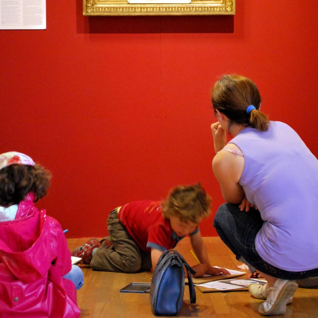 A droite de cette image, une femme est accroupie, de dos. Elle porte un petit haut violet et un jean. Elle aide son fils qui travaille installé par terre dans la salle d'exposition des Jacobins. A gauche, une petite fille assise, de dos qui porte un manteau rose est en partie visible. Les trois personnes sont face à un mur rouge sur lequel la baguette dorée du bas d'un tableau apparait.